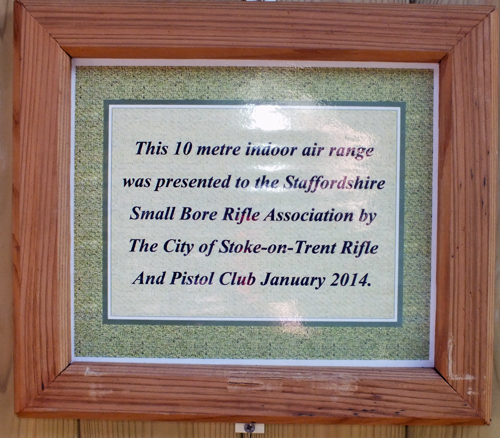 Photograph shows the dedication plaque fixed to the Airgun Range, in appreciation of The City of Stoke-on-Trent Rifle And Pistol Club's very kind gesture of presenting the Indoor 10 Metres Air Weapons Range to the Staffordshire Smallbore Rifle Association in January 2014.