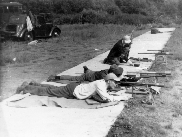 Photograph shows competitors settling down prior to shooting on the exposed firing points.